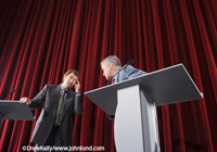 Picture of a debate between two politicians. The men are standing on a theater stage with podiums in front of them. The two men are facing each other as they debate. Behind the men are tall red velvet theater curtains.